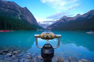Gooi er een muntje in en zie Lake Louise en de bergen van dichtbij!