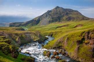 Het groene en glooiende landschap van IJsland nodigt uit tot avontuurlijke wandelingen.