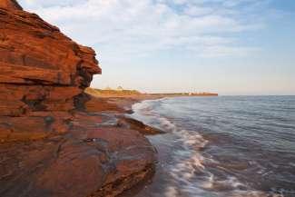 Kilometerlange Küstenlinie so weit das Auge reicht, dazu leuchtend roter Boden.
